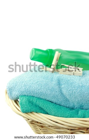 Laundry basket with fresh towels, laundry soap and clothespins isolated on white. - stock photo