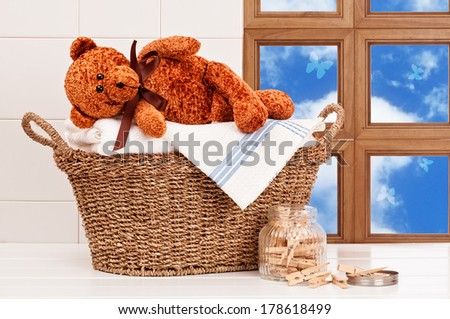 Laundry basket with freshly laundered white towels and teddy bear - stock photo