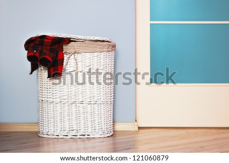 Laundry basket with red shirt on pine floor - stock photo