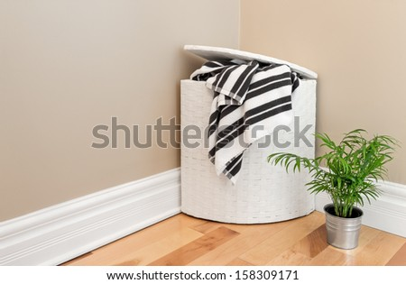 Laundry basket with striped towels and green plant in the room corner. - stock photo
