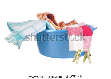 Laundry - blue wash-basin with clean clothes and clothespins - stock photo