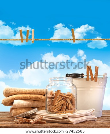 Laundry day with towels, clothespins on table against blue sky - stock photo