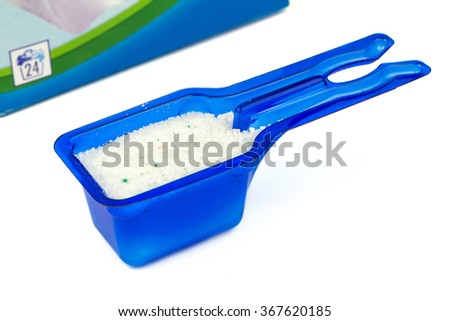 Laundry detergent or washing powder in blue measuring cup studio isolated - stock photo