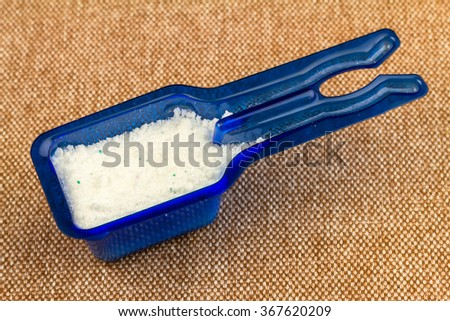 Laundry detergent or washing powder in blue measuring cup, top view - stock photo