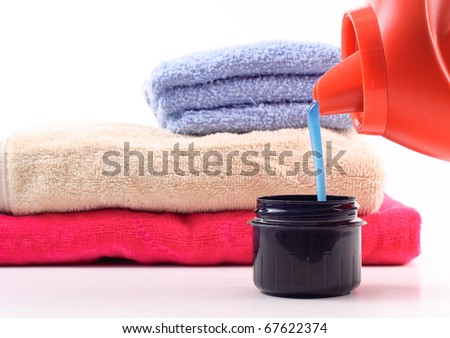 Laundry Detergent Pouring Into Measuring Cap - stock photo