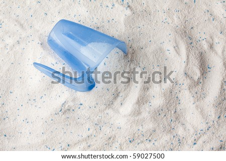 Laundry detergent powder for washing machine and plastic scoop for dosage. - stock photo