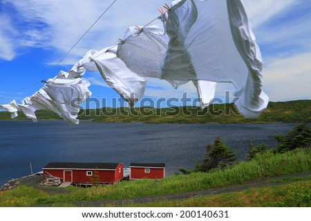 Laundry drying on the clothesline near red cabin in beautiful Nordic landscape - stock photo