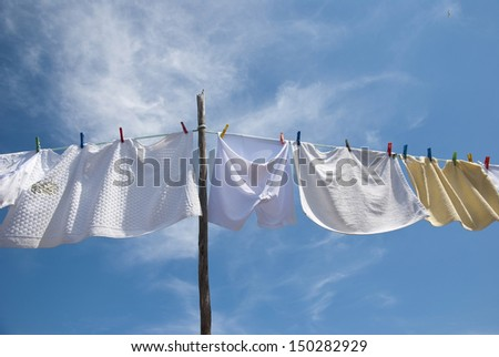 Laundry drying on the rope outside on a sunny day - stock photo