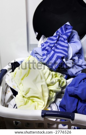 Laundry falling out of a washing machine into a basket - stock photo