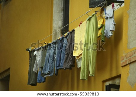 Laundry hanging on a clothes line on a bright yellow building in Venice, Italy.