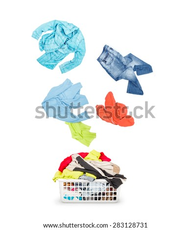 Laundry in a basket and falling clothes - isolated on a white  - stock photo