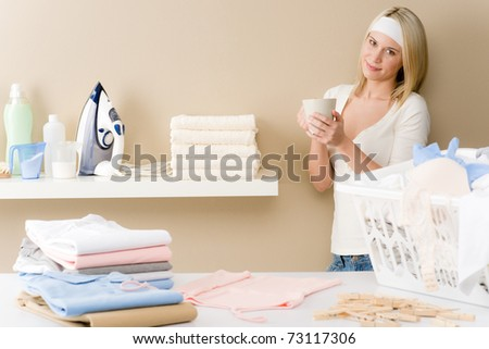 Laundry ironing - woman coffee break after housework - stock photo