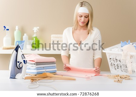Laundry ironing - woman folding clothes, housework - stock photo