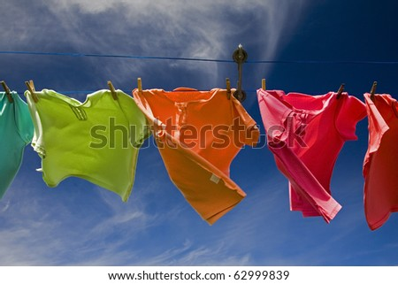 Laundry of pastel colored shirts drying in the wind - stock photo
