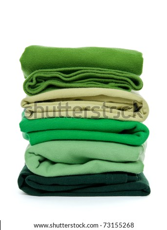 Laundry - pile of green folded clothes on white background. - stock photo