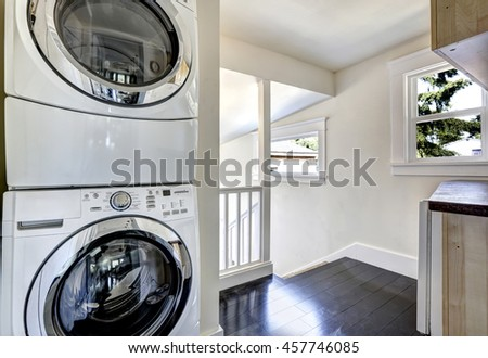 Laundry room with modern white appliances. Hallway