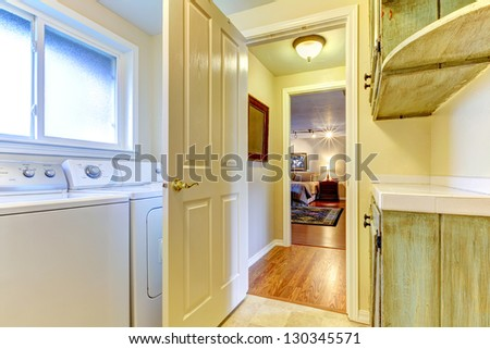 Laundry room with open door to bedroom and green cabinets. - stock photo