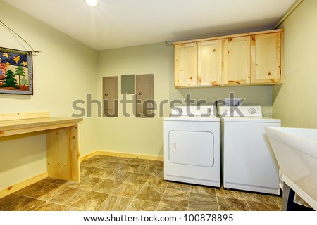Laundry room with sink and folding desk and green walls. - stock photo