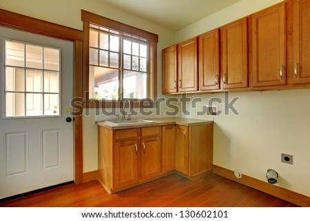 Laundry room with sink and wood cabinets.  New luxury home interior. - stock photo