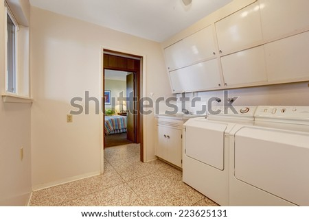 Laundry with built in cabinets, old washer and dryer - stock photo