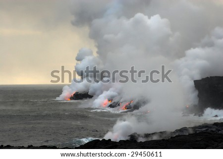 Lava erupting into Pacific Ocean during evening on Big Island - stock photo