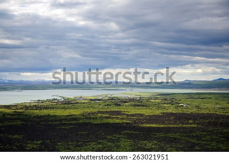 Lava field and small village near Myvatn lake on a cloudy summer day, North Iceland - stock photo