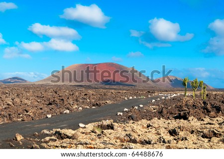 Lava Fields and a road leading to the mountains of fire, Timanfaya National Park in Lanzarote Island - stock photo