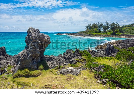 Lava rock formations and pristine turquoise colored water along the coastline of Bermuda. - stock photo