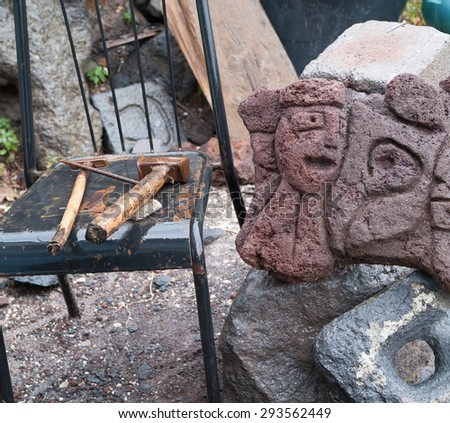 Lava stone sculpture of a stylised woman's face on the worktable of an artisan and tools on a chair
