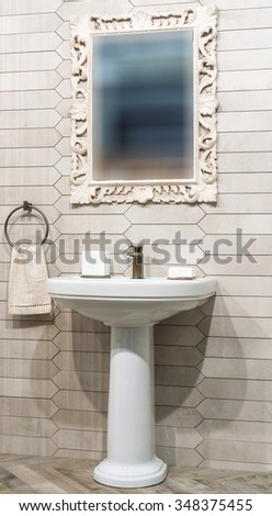 Lavatory and mirror in bathroom interior - stock photo