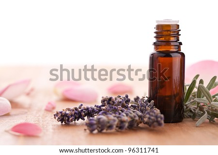 lavendel and parfum bottle with rose leafs on wooden background - stock photo