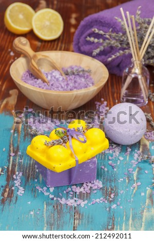 Lavender and lemon aromatherapy. Natural handmade lavender oil, soaps with bath salt,  foaming bath bomb, lemon and lavender on wooden background. Macro, selective focus.  - stock photo