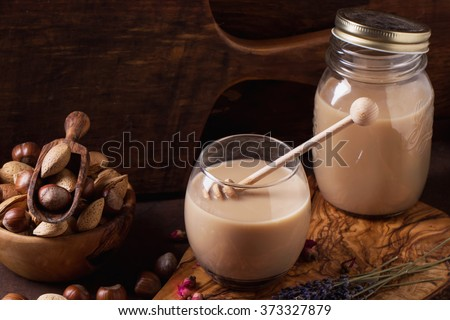 Lavender and rose infused hazelnut non-dairy milk served with nuts and flowers on olive tree wooden board. Dark rustic  style