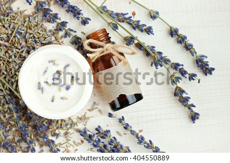 Lavender aroma oil, bottle with empty label and twine bow, herbal facial moisturizer cream, dried lavender flower sprigs. Handmade herbal skincare products. Top view. - stock photo