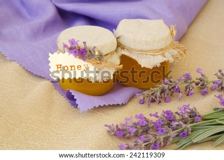 Lavender blossom honey. Lavender twigs in the background. - stock photo