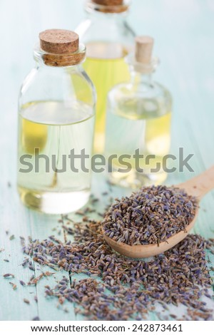 Lavender buds and essential aroma oil with lavender on wooden background. Selective focus. - stock photo