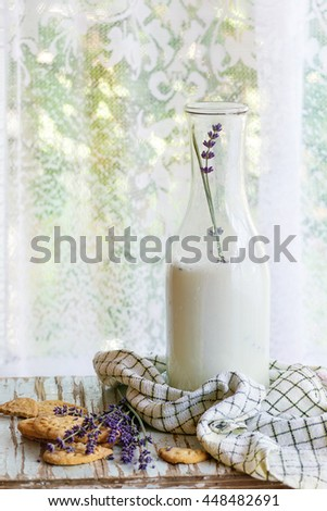 Lavender cookies and bottle of aromatic milk, served with kitchen towel on old wooden table with window at background. Breakfast in rustic style, natural day light. - stock photo