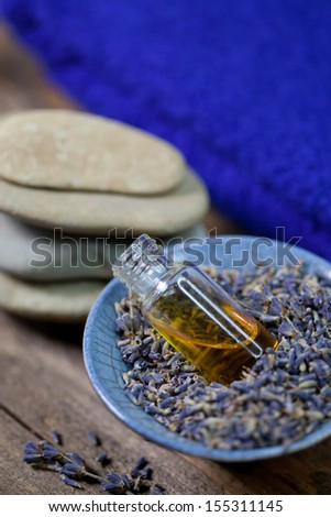 Lavender essence in a bowl and zen stones - stock photo