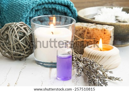 Lavender Essential Oil Bottle .Spa Setting with Burning Candles,Soap and Towel - stock photo
