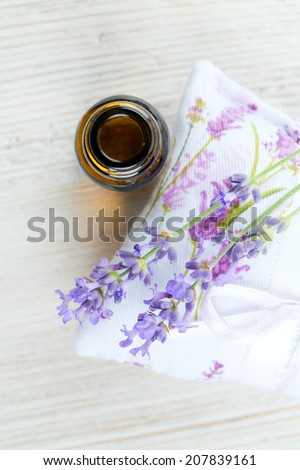 lavender essential oil on wooden surface - stock photo