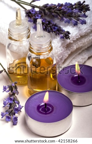 Lavender essential oil, scented candles and fresh flowers - stock photo