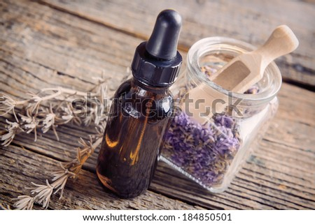 Lavender essential oil with lavendula flowers in the jar, dry leaves of this herb near the bottle. - stock photo