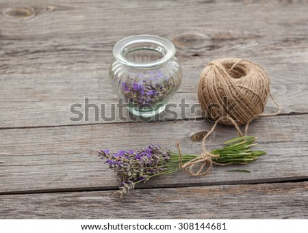 Lavender flowers and glass bottle on wooden background.  - stock photo