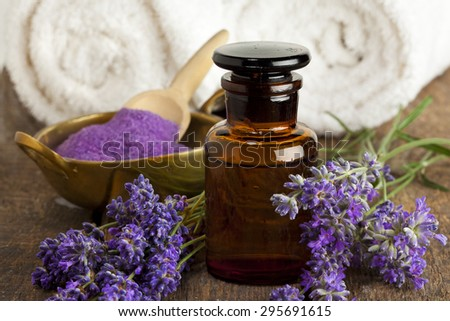 Lavender flowers, apothecary bottle, bowl of bath salt and towels - stock photo