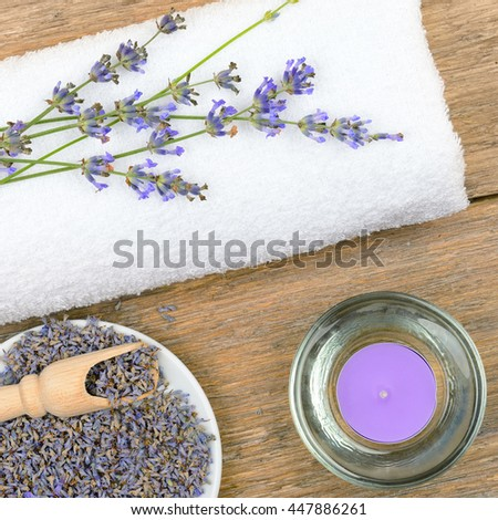 lavender flowers, aromatic candles, and towels on wooden background - stock photo