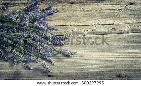 Lavender flowers on wooden background. Country style still life. Vintage toned picture - stock photo