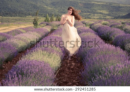 Lavender goddess. Beautiful young woman posing in a lavender field. Wind blows her hair. Her arms folded over chest. - stock photo