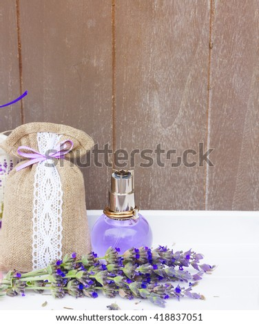 Lavender herbal  water, fresh flowers and dry in pouch, copy space on gray wooden background  - stock photo