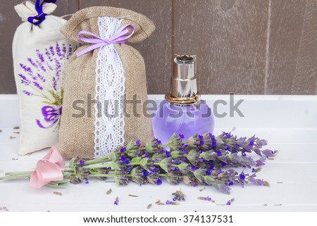 Lavender herbal water in a glass bottle, fresh flowers and dry in pouch - stock photo