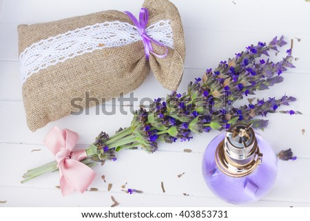 Lavender herbal water in a glass bottle with fresh and dry flowers in pouch on white wooden table - stock photo